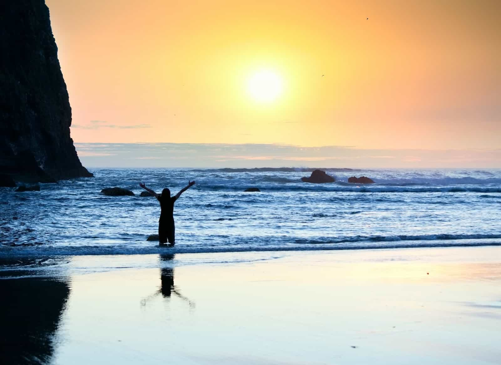 9572304_girl-standing-in-waves-arms-raised-to-sky-at-sunset