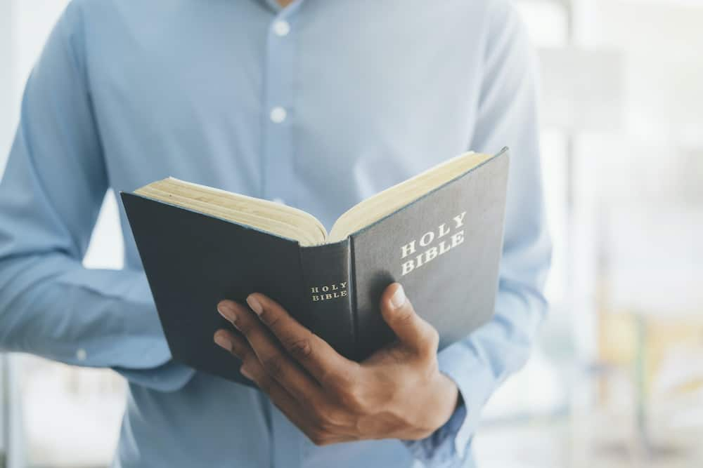 Religion Christianity concept. Man holding and reading the holy Christian Bible.